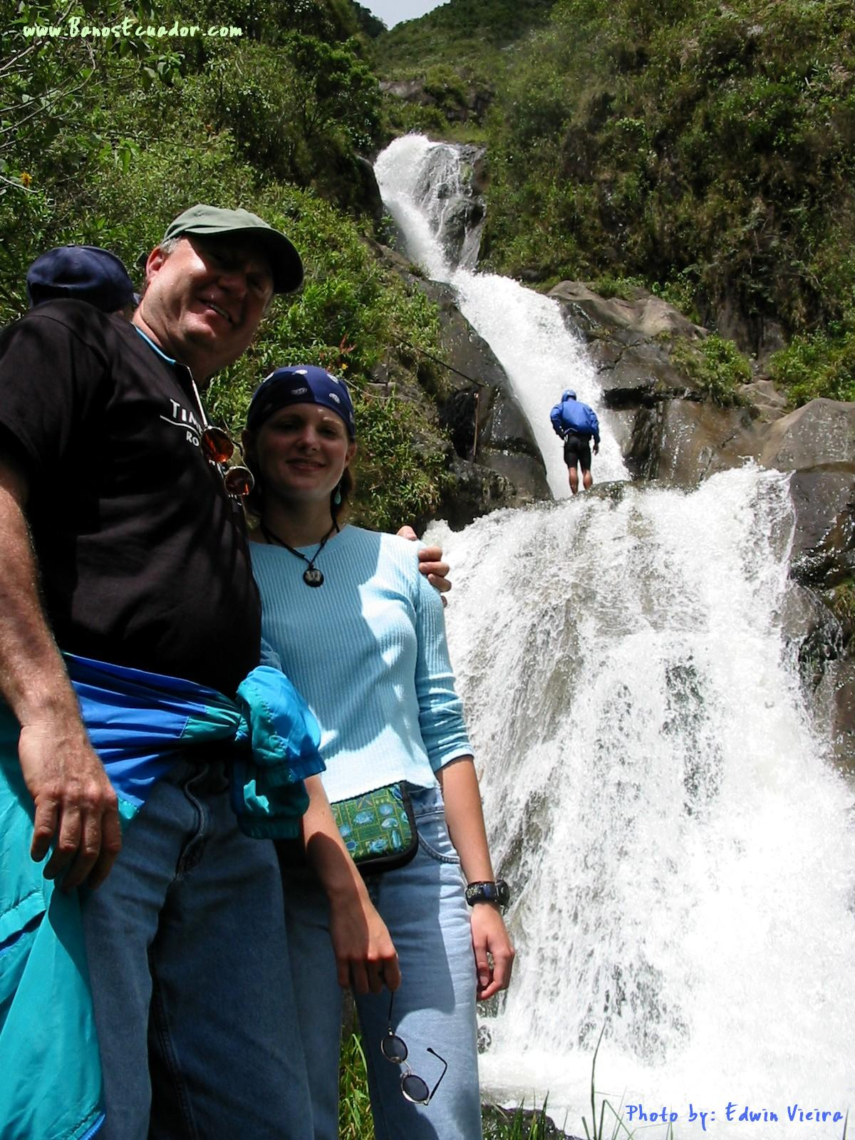 two people smiling, a man and a woman standing in front of a waterfall in a sunny day.